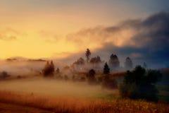 Village brumeux au crépuscule Photographie stock
