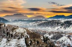 Village brumeux sous les montagnes en hiver Photo libre de droits