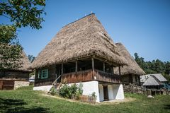 Traditional Romanian village home with hay grass roof. royalty free stock photo