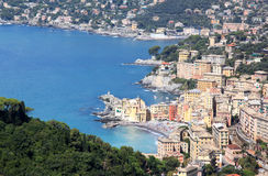 Village of Camogli along the Golfo Paradiso, Italy. Sunbathers in the Italian village of Camogli, situated on on a rocky outcrop on the west side of the Royalty Free Stock Image