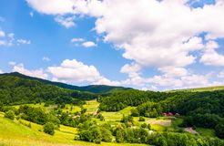 Village in Carpathian mountains in summertime. Lovely rural scenery under the blue sky with clouds royalty free stock image
