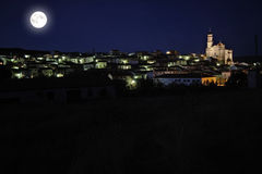 Village with cathedral under the moon Stock Image