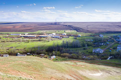 Village, cattle farm and a drilling rig in the field. Photographed in Russia, in the Orenburg region, in the village of Repino. Village, cattle farm and a Stock Photos