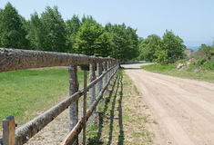 Village cattle-pen with wooden fence along the road Stock Photos