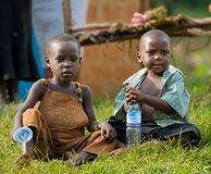 Village children are sitting at the roadside. Royalty Free Stock Image