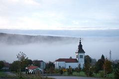 Village with church. Morning village with church and fog in background Stock Images