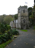 Village church in Cornwall. Village church flying the Cornish flag of St Piran beside river and estuary stock image