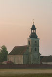 Village church. Small rural church in the morning mist.. Photo taken in June by sunrise. Idyllic rural landscape in the warm sunshine.  Country: Poland, Region Stock Images