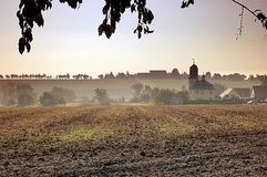 Village church to Romschütz. View over fields to a small village with church at early in the morning Stock Photos
