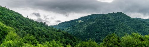 A village courtyard atop a mountain on a rainy day in the summer. Panoramic view of the green Carpathian Mountains in summer royalty free stock image