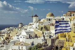 Village d'Oia contre le drapeau de ondulation grec sur l'île de Santorini photo stock