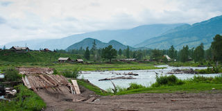 Village de Kucherla, pont en bois à travers la rivière de montagne Photos libres de droits