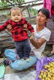 Village de Lobesa, Punakha, Bhutan - 11 septembre 2016 : Homme non identifié avec son bébé sur son recouvrement au marché hebdoma Image stock