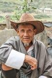Village de Lobesa, Punakha, Bhutan - 11 septembre 2016 : Vieil homme de sourire non identifié avec le chapeau se reposant au marc Photos stock
