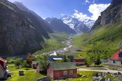 Village de montagne été et crêtes de montagne neigeuses Images stock