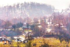 Village de montagne authentique sur des collines Temps brumeux et neige de fonte image libre de droits