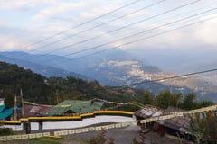 Village de montagne de Gangtok avec les arbres verts, ciel bleu et fil qui regardent le niveau supérieur de forme du monastère de Photographie stock libre de droits