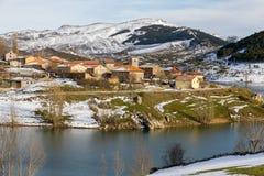 Village de neige de montagne sur la pente d'un réservoir en hiver Image stock