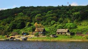 Village de pêche sur la banque de la rivière dans vieil en bois de forêt verte Image libre de droits