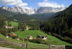 Village in the Dolomites. Village in a valley in the Dolomites, Italy, with Rosengarten mountains in background Royalty Free Stock Photo