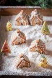 Village doux fait maison de pain d'épice de Noël avec le bonhomme de neige et les arbres Photo libre de droits