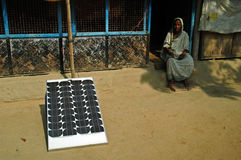 Village electrification. A solar panel is installed in front of a hut belongs to this old village woman as a part of electrification through renewable energy in