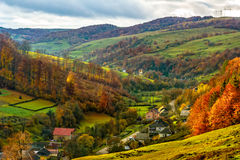 Village falls on hillside with autumn forest in mountain Royalty Free Stock Image