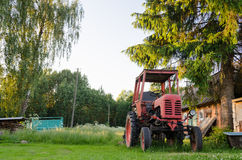 Village farm red old tractor in meadow summer time Royalty Free Stock Photo