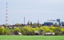 The village with field on the background of the agricultural complex, grain warehouse. And communication tower stock photos