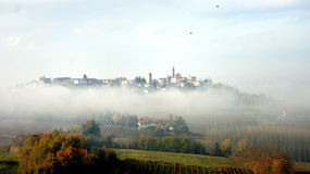 Village in the fog. Village on the hilltop surrounded by fog, Piedmont, Asti, Italy Royalty Free Stock Photo