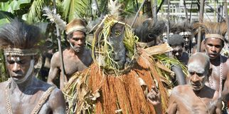 The Village follows the ancestors embodied in spirit mask as they tour the village Stock Image