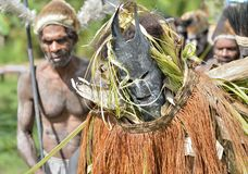 The Village follows the ancestors embodied in spirit mask as they tour the village Stock Images