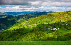 Village on a forested hillside in springtime. Beautiful rural scenery of Carpathian mountains on a cloudy day royalty free stock photography