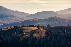 Village on forested rolling hill in haze. Beautiful countryside scenery in mountain of Romania at sunrise Royalty Free Stock Photos