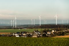 Village in front of panorama view over wind farm landscape in Germany with white generator turbines. Village in front of A panorama view over a wind farm Stock Photography