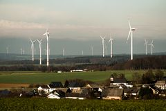 Village in front of panorama view over wind farm landscape in Germany with white generator turbines. Village in front of A panorama view over a wind farm Royalty Free Stock Image