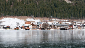 Village at the frozen mountain lake Stock Image