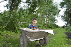 In a village in the garden boy sitting in the cart. Stock Photo