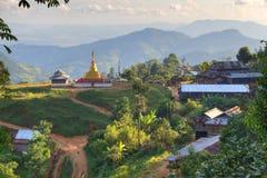 Village with golden stupa an green hills Stock Photo