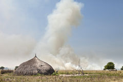 Village and grassfire in South Sudan Royalty Free Stock Photos