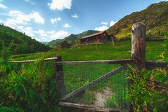 Village and  grassland in mountains. Wide-angle shooting of abandoned houses in forsaken village in mountains with pasture and wooden fence and Rabitz-type steel Royalty Free Stock Images