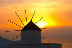 Village grec traditionnel, Oia, Santorini, coucher du soleil avec le winmill Photographie stock libre de droits