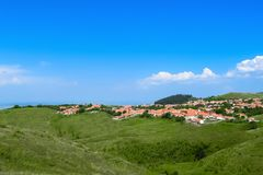 Village on a green hill, Romania. A village on a green hill on a clear summer day, Romania Stock Photo