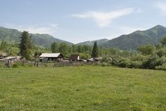 Village in the mountains of Russia. Village among green hills, wooden old houses, summer, beautiful landscape Royalty Free Stock Photography