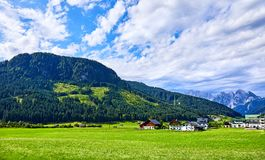 Village among green meadows and Austrian Alps. Traditional village among meadows, fields and Austrian Alpine mountains. Knolls covered with green forests and Royalty Free Stock Image