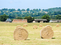 Village and haystack rolls on field in Normandy. France stock images