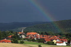 Village of Herleshausen with a rainbow after a summer thunderstorm Royalty Free Stock Photography