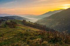 Village on the hill and in valley full of fog. Beautiful mountainous countryside at dawn. village on the hill and in valley full of fog. wonderful autumn stock photos