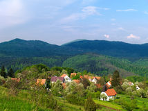 Village among hills. Small village among colorful hills in springtime Stock Photo