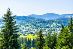 Village in the hills. Ukrainian village Kosmach in the hills of Carpathian mountains. Houses, clay roads, fields and forest in frame. A sunny day at the end of royalty free stock photography